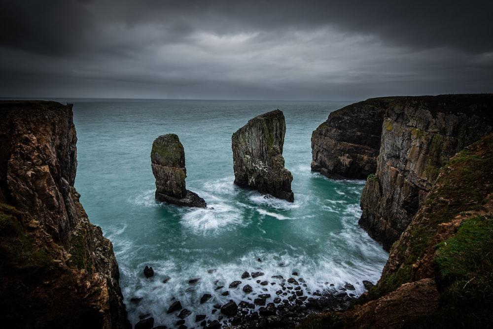 gray coastal rocks under cloudy sky during daytime