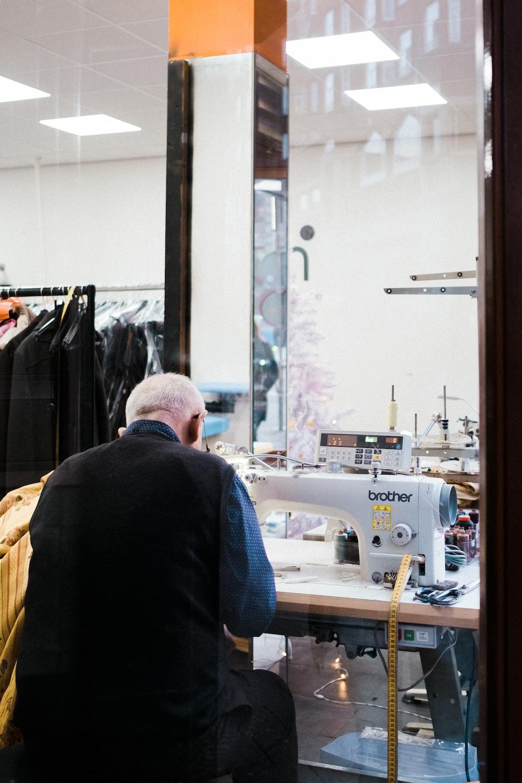 sitting man sewing