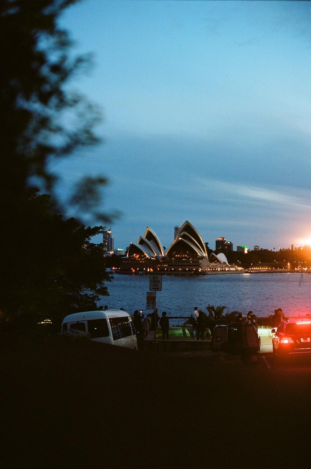 people gathering near body of water beside Sydney Opera House