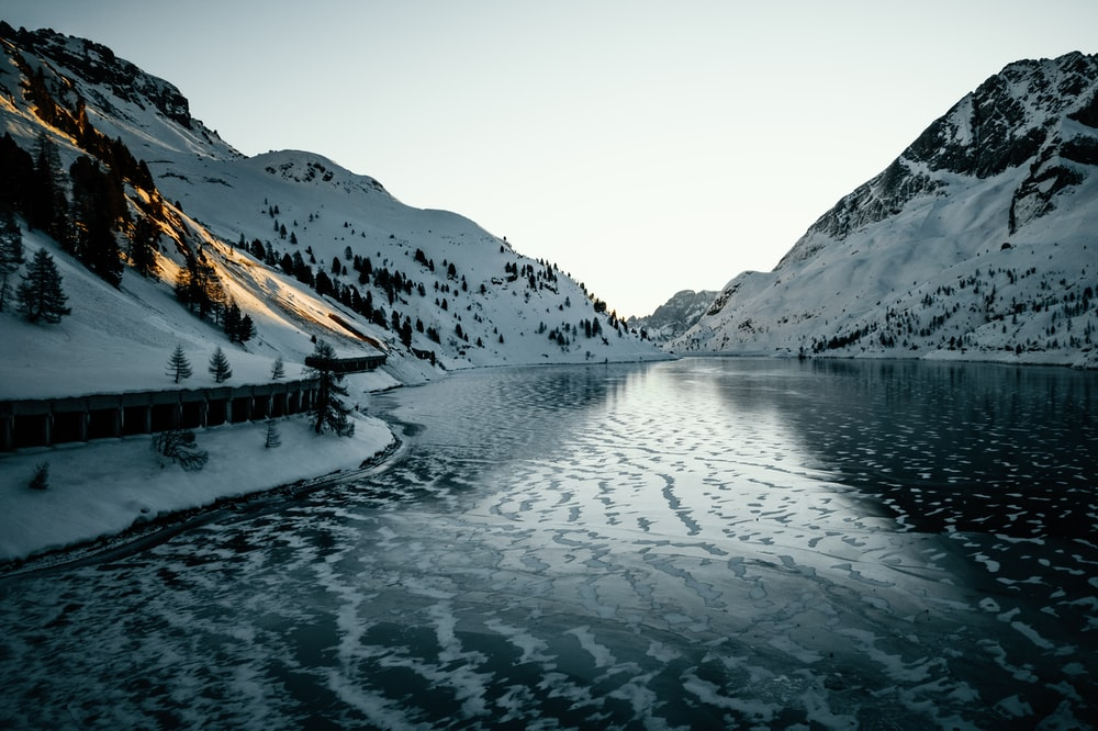 calm body of water and mountain covered with snow