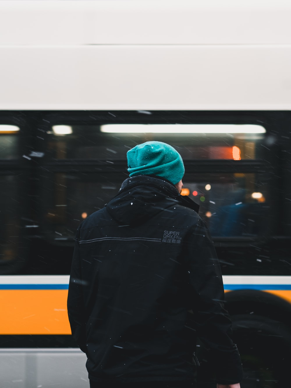 unknown person in black hoodie and teal knit cap