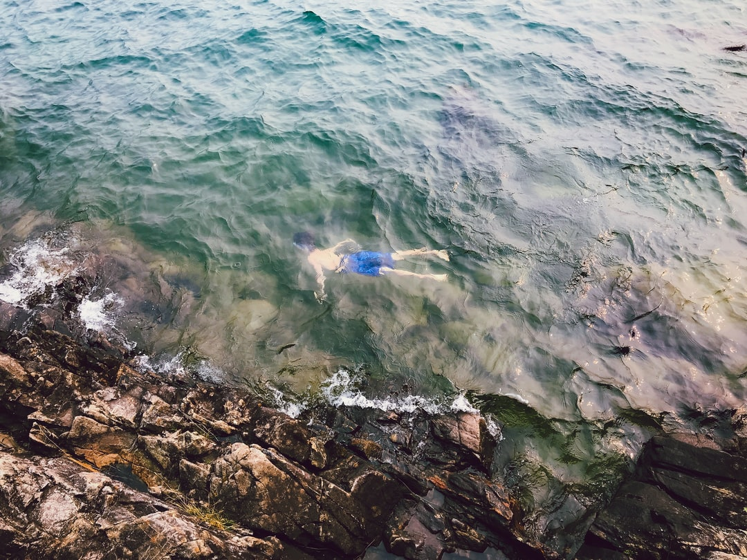 person swimming near rocks below the water surface with waves all around