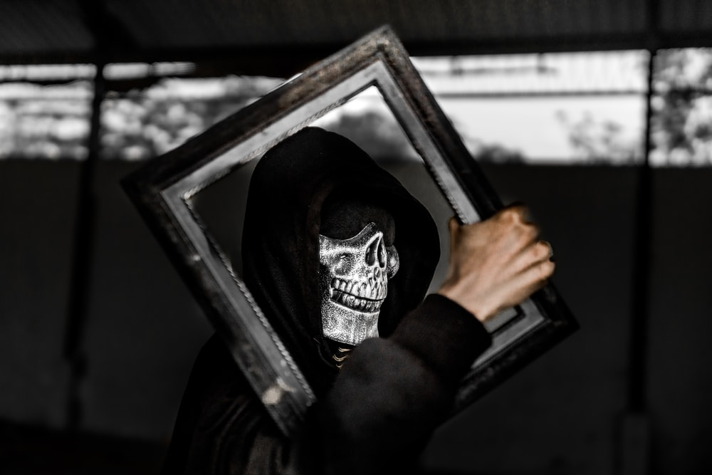 grayscale photography of person wearing skull mask standing while holding rectangular wooden frame