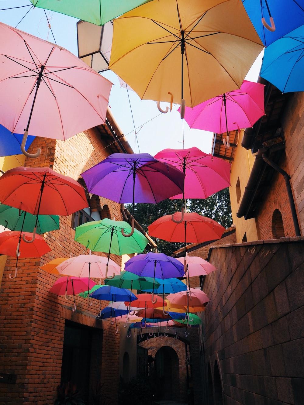 assorted-color umbrella hanging beside building