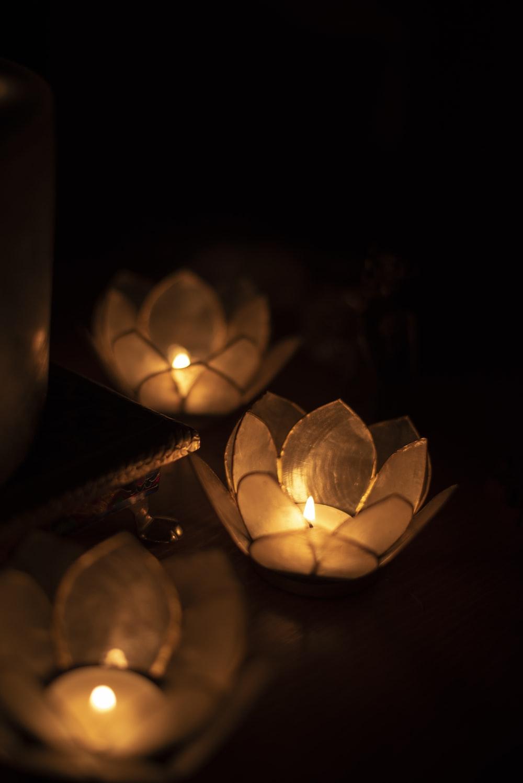 three lighted yellow tealights