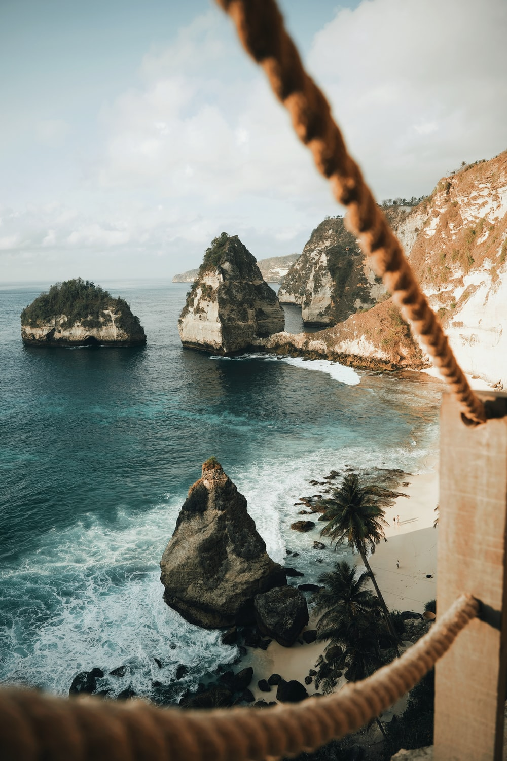 wide-angle photography of mountain cliff beside seashore during daytime