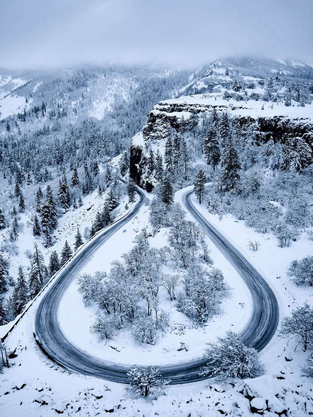 aerial photography of empty road and snow-covered field during daytime