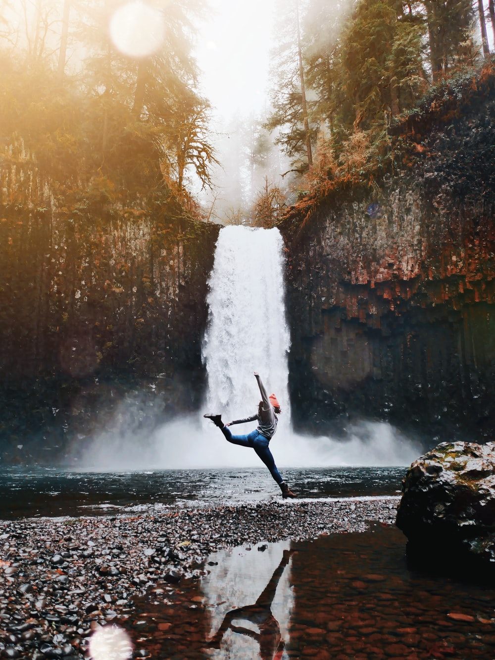 woman jumping in front of waterfalls during daytime