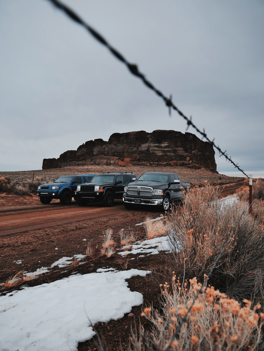 three black SUV on the field with rock formation