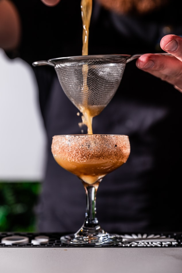 Kaffeecocktail wird in ein Glas abgeseiht