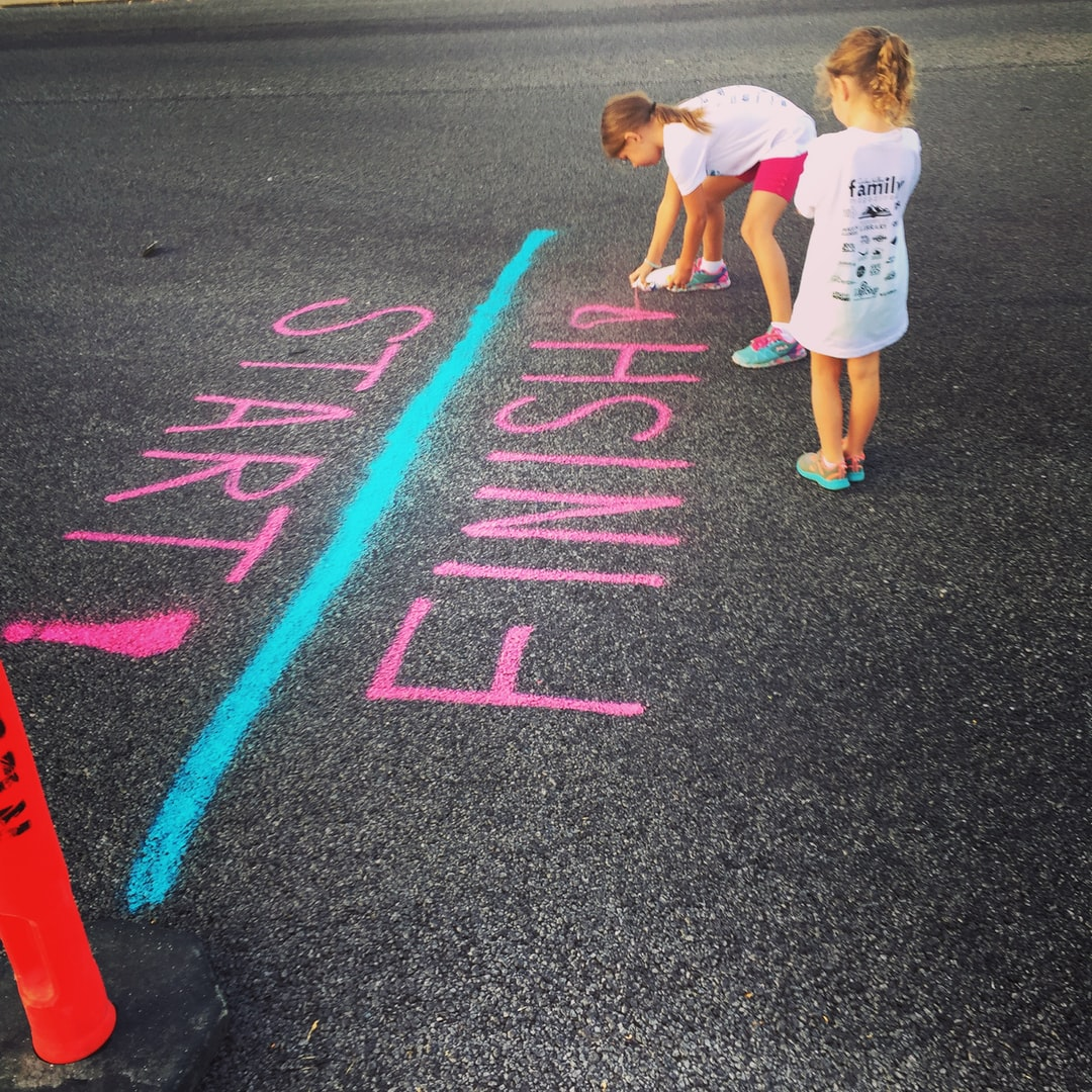 Two young girls mark a start/finish line using bright pink spray paint. Their efforts help get everything ready for a summertime 5k race in northern Utah.   https://www.instagram.com/AwCreativeUT/ https://www.awedcreative.com/ https://www.awcreativeut.com #AwCreativeUT #awcreative