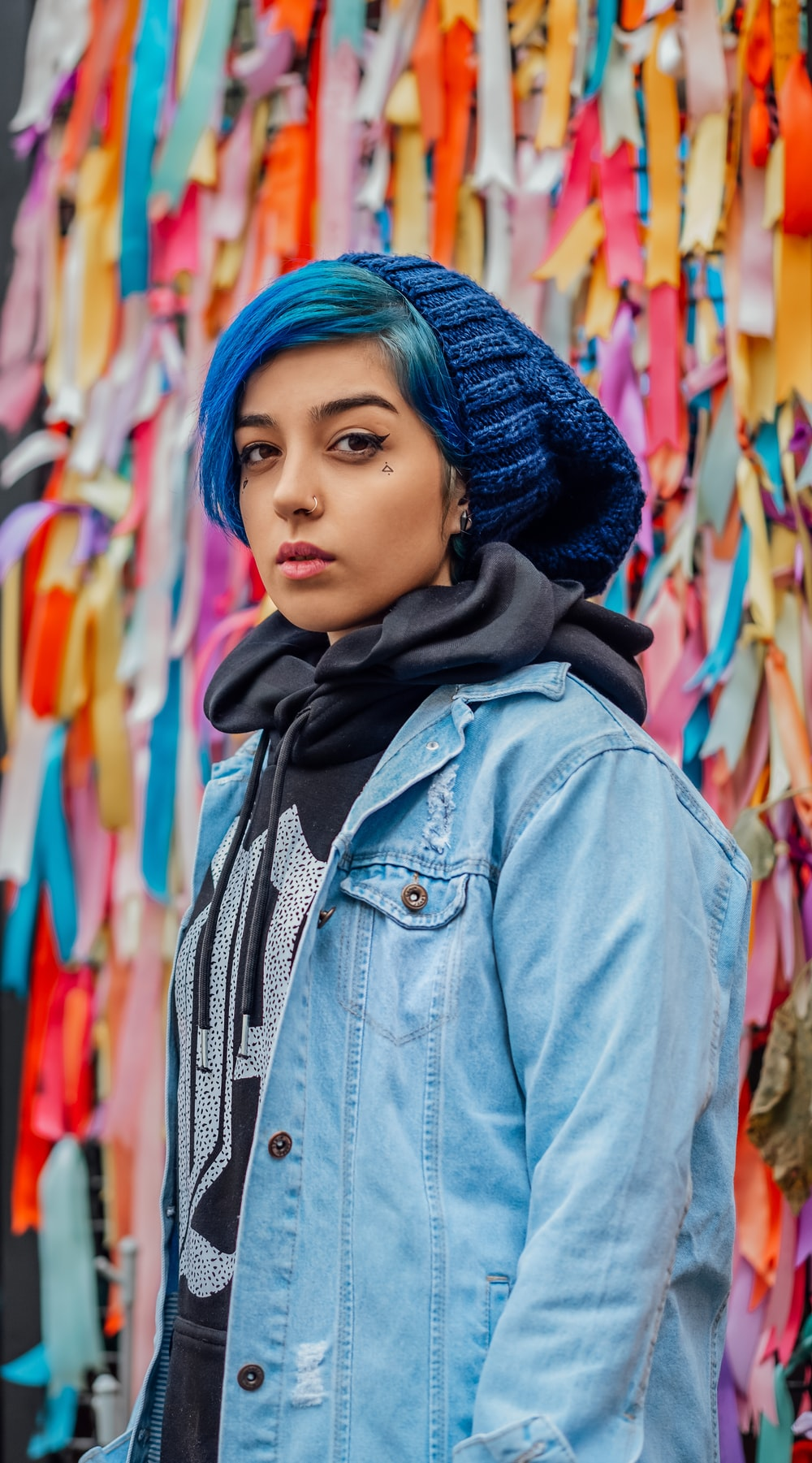 woman with blue hair wearing blue denim jacket standing beside wall with bows