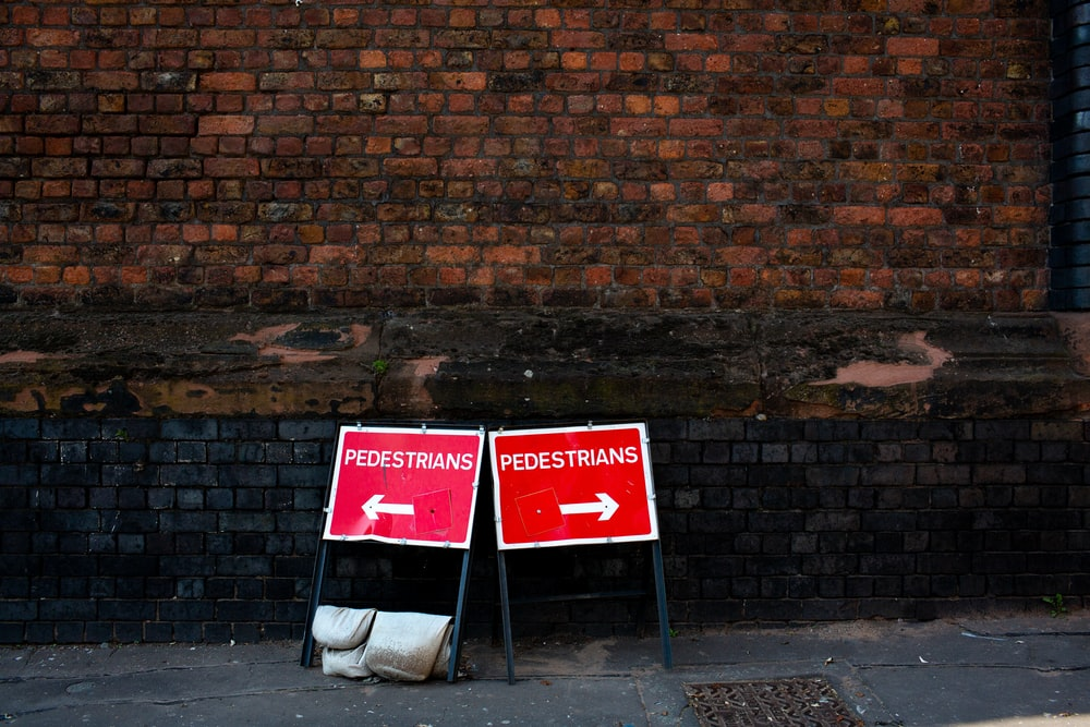 two pedestrians signs beside brown brick building