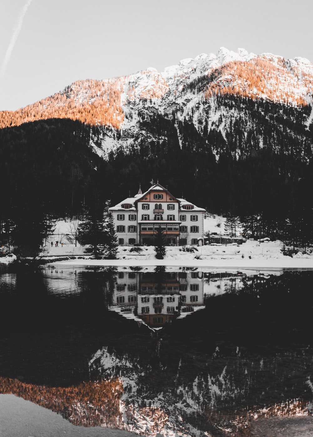 white and brown house near body of water