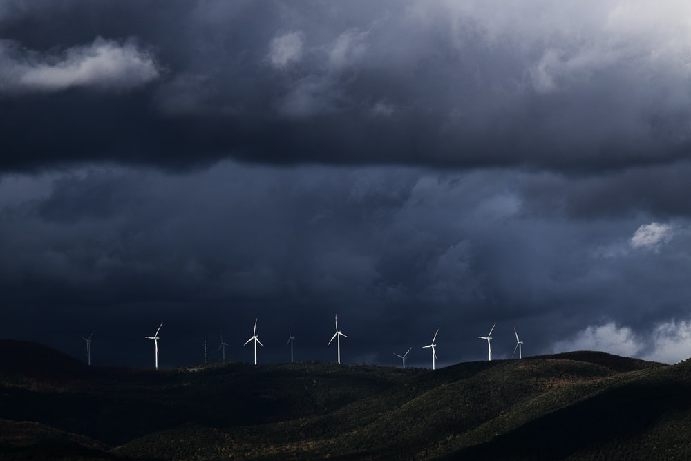 wind turbines on hill under heavy clouds