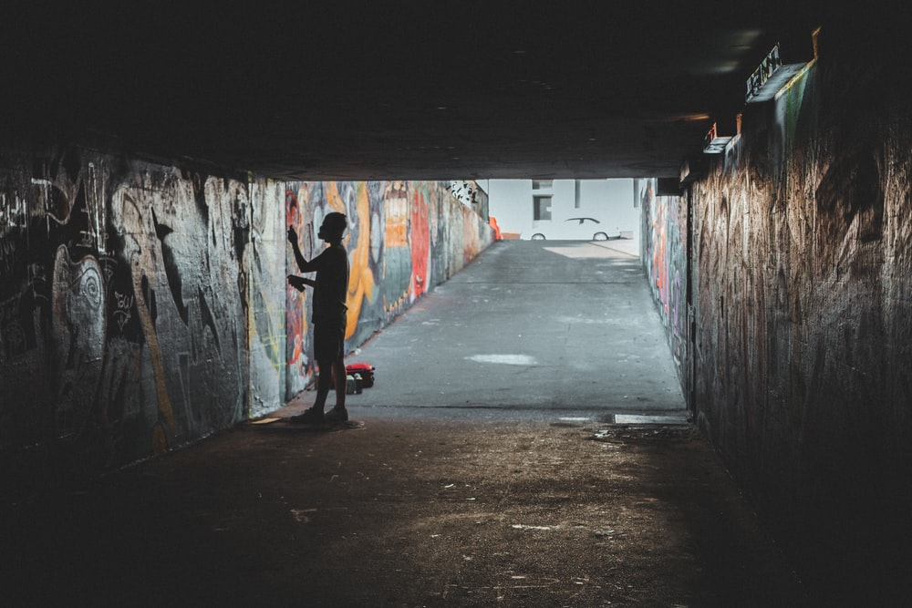 person standing inside tunnel with murals