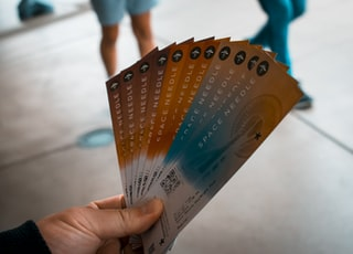 person holding brown, blue, and white tickets