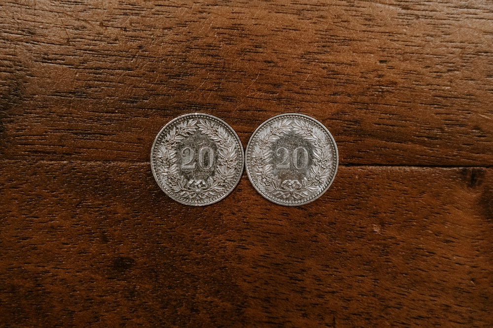 two round silver-colored 20 coins on brown surface