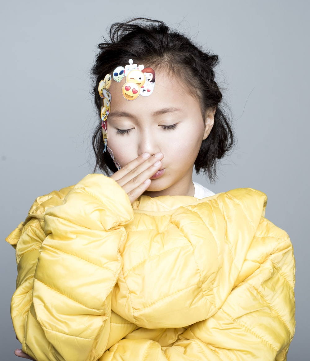 closed eyed girl covering her mouth with her hand