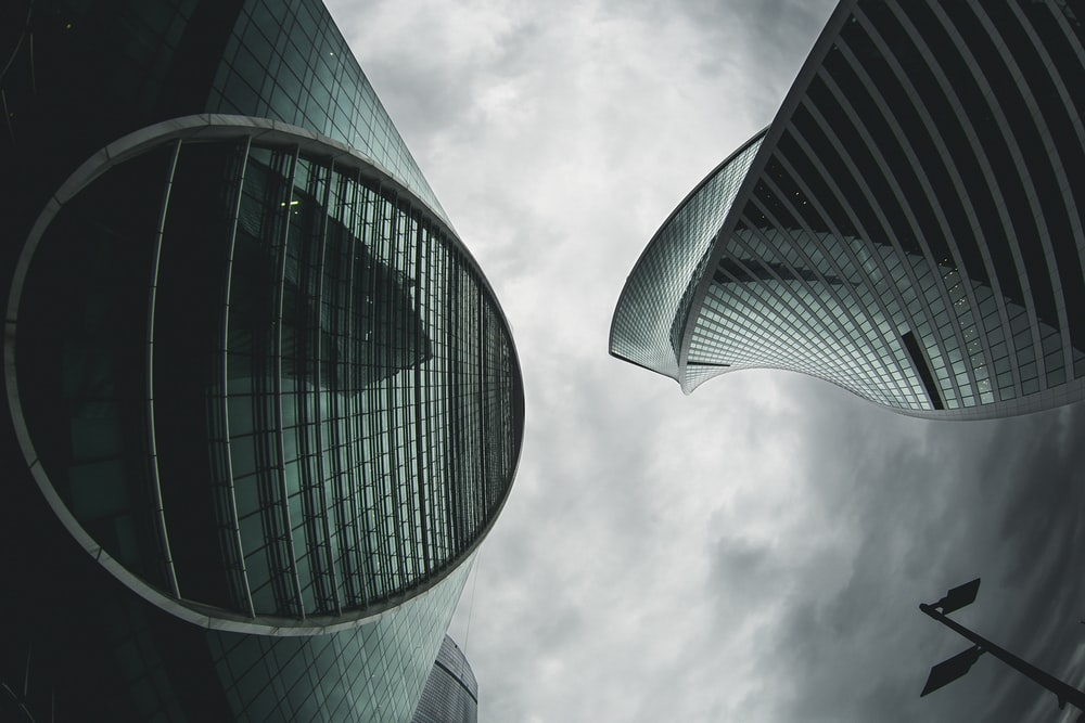 architectural photography of green high-rise buildings under white and gray sky