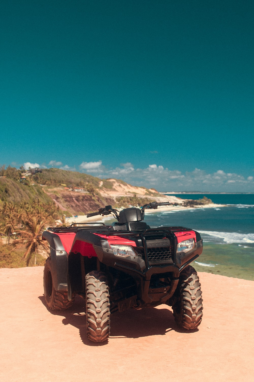 red and black ATV on the beach