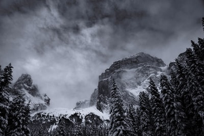 grayscale photography of summit view of mountain covered with snow tempest teams background