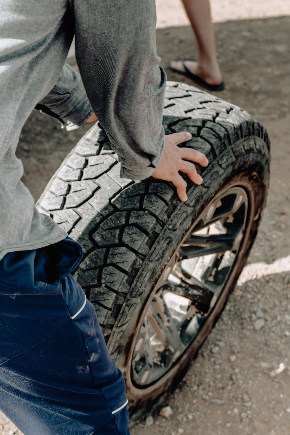 person holding vehicle wheel and rim