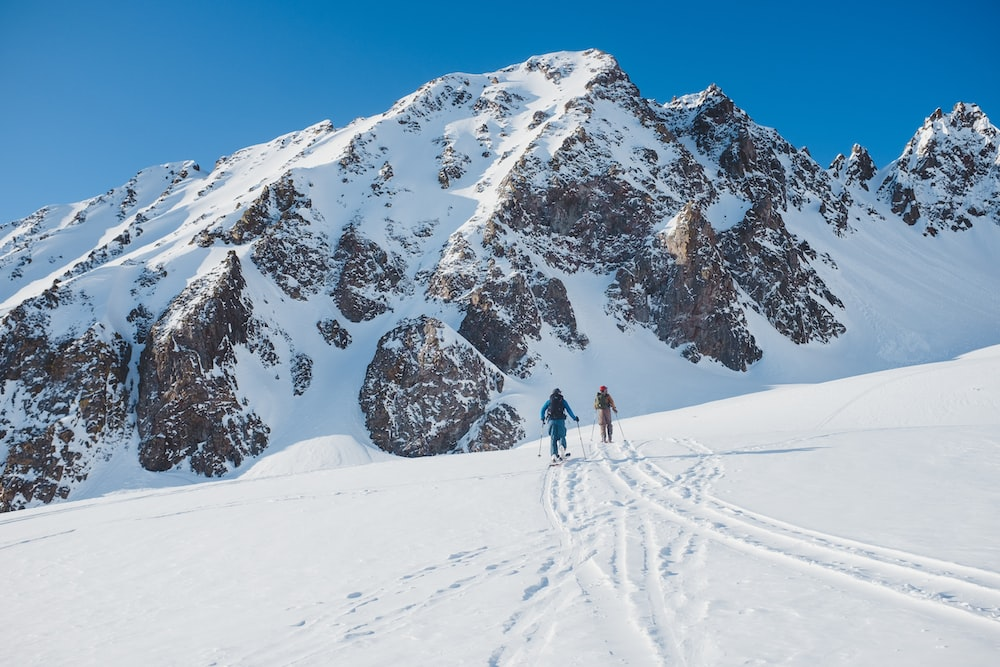 two people skiing on snowy field viewing mountain covered with snow during daytime