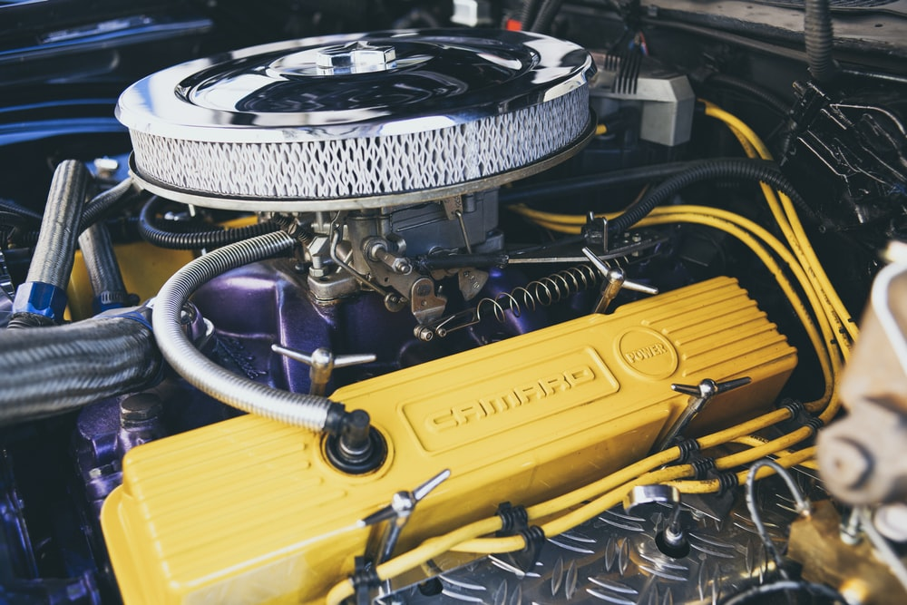shallow focus photography of yellow and gray car engine bay
