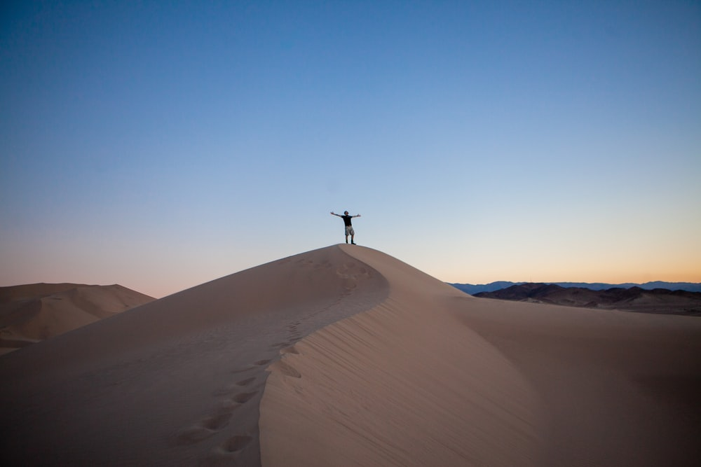person raising both hands while standing on desert under blue and white sky