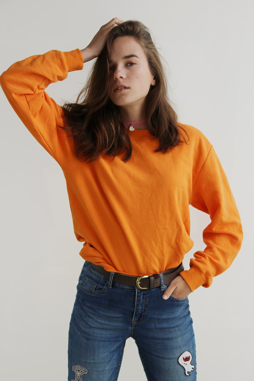woman wearing orange crew-neck sweatshirt standing while putting right hand on her head