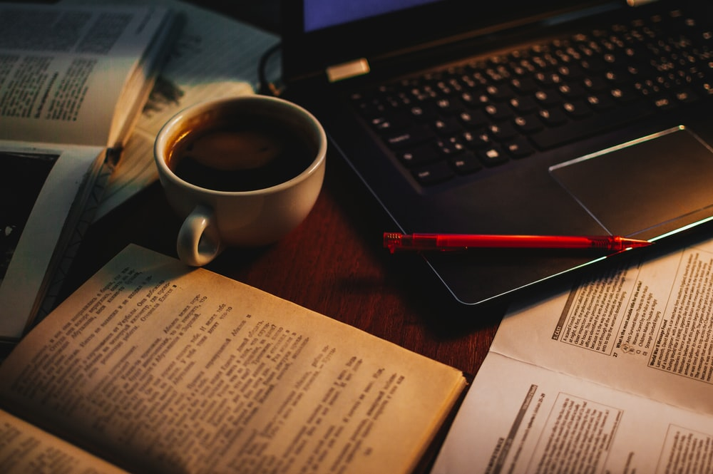 cup of coffee in between of open book and black laptop