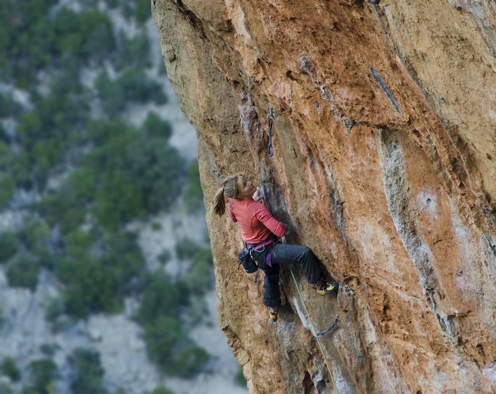 woman climbing on rock cliff