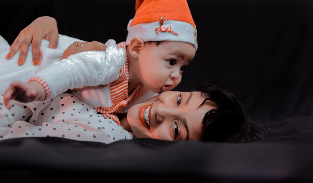 woman hugging baby while lying on bed
