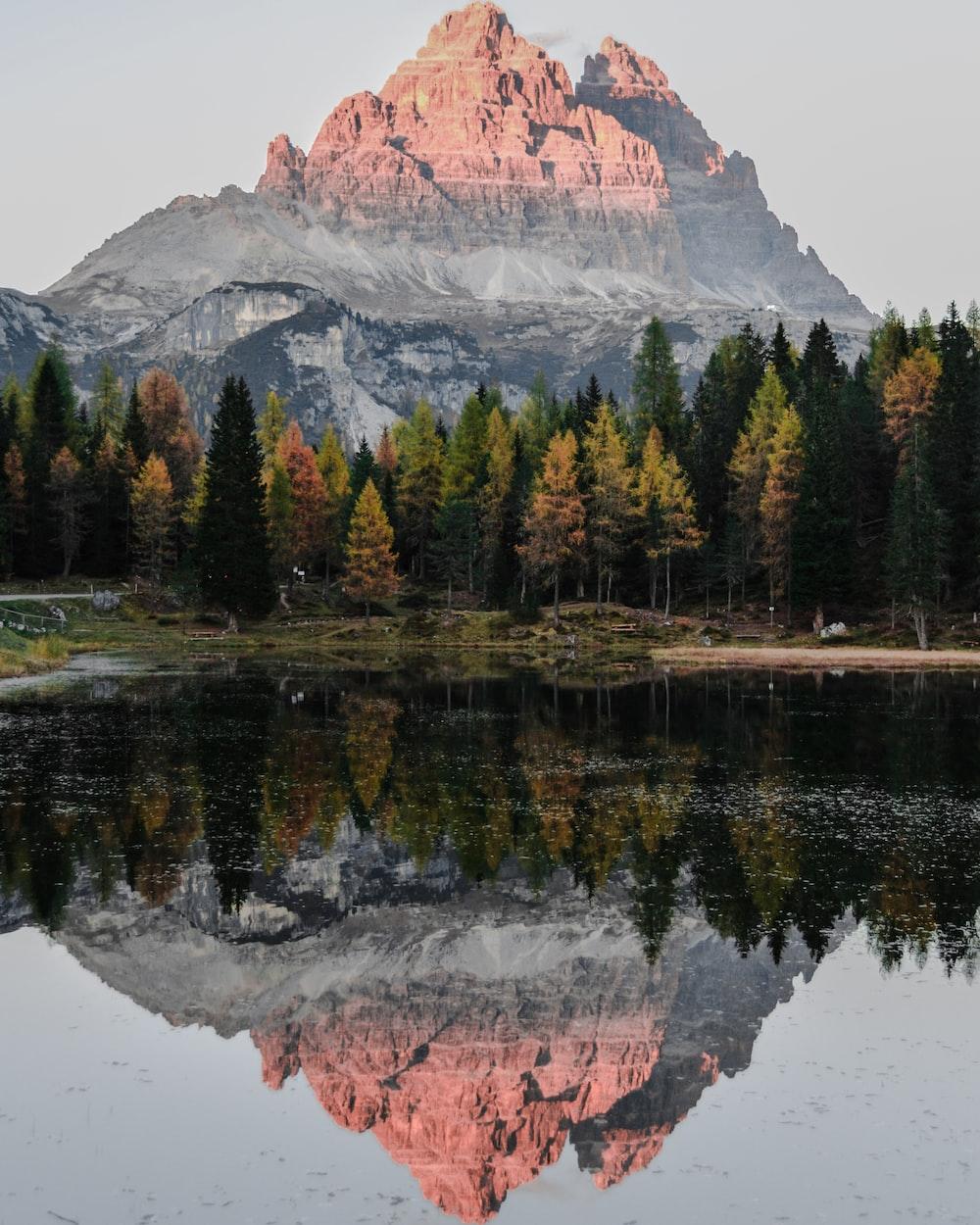 water reflect photography of mountain ridge