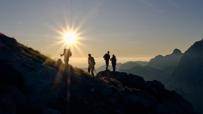 four person on mountain during daytime hiking teams background