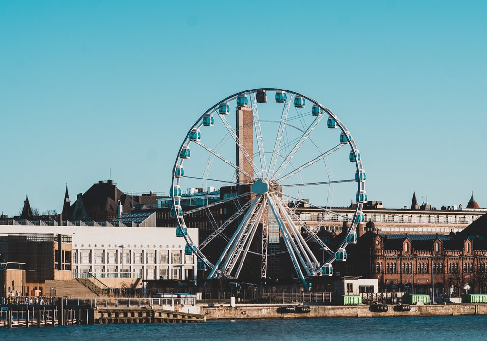 Ferris wheel near buildings facing body of water