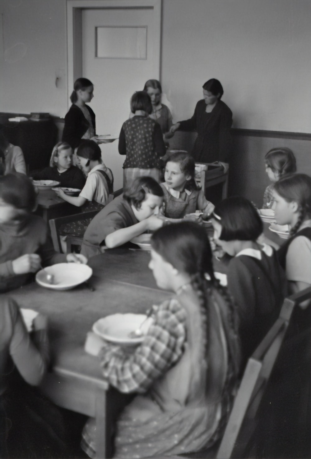 grayscale photography of children sitting while eating near table