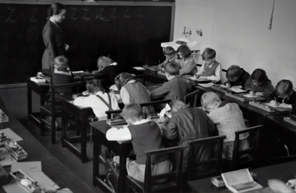 grayscale photography of teacher standing near chalkboard and children sitting on chairs