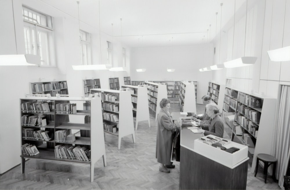 grayscale photography of people inside book store