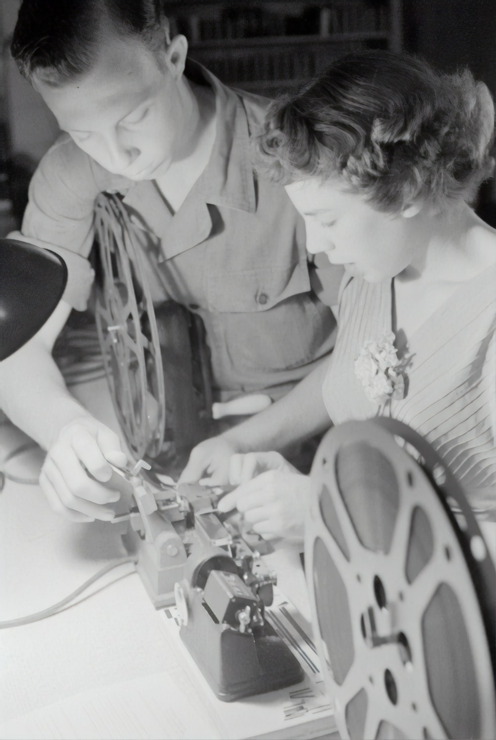 grayscale photography of man assisting woman while fixing film reel
