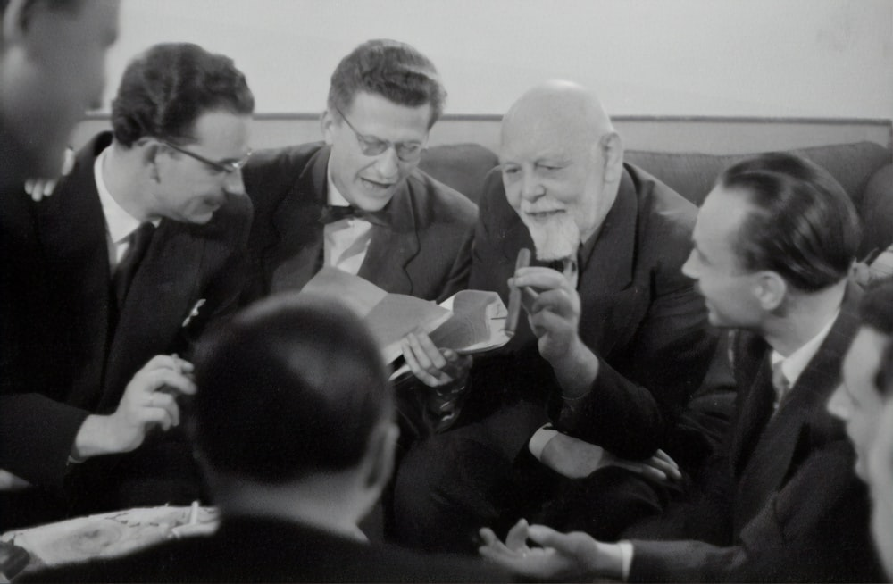 grayscale photography of group of men sitting and chatting