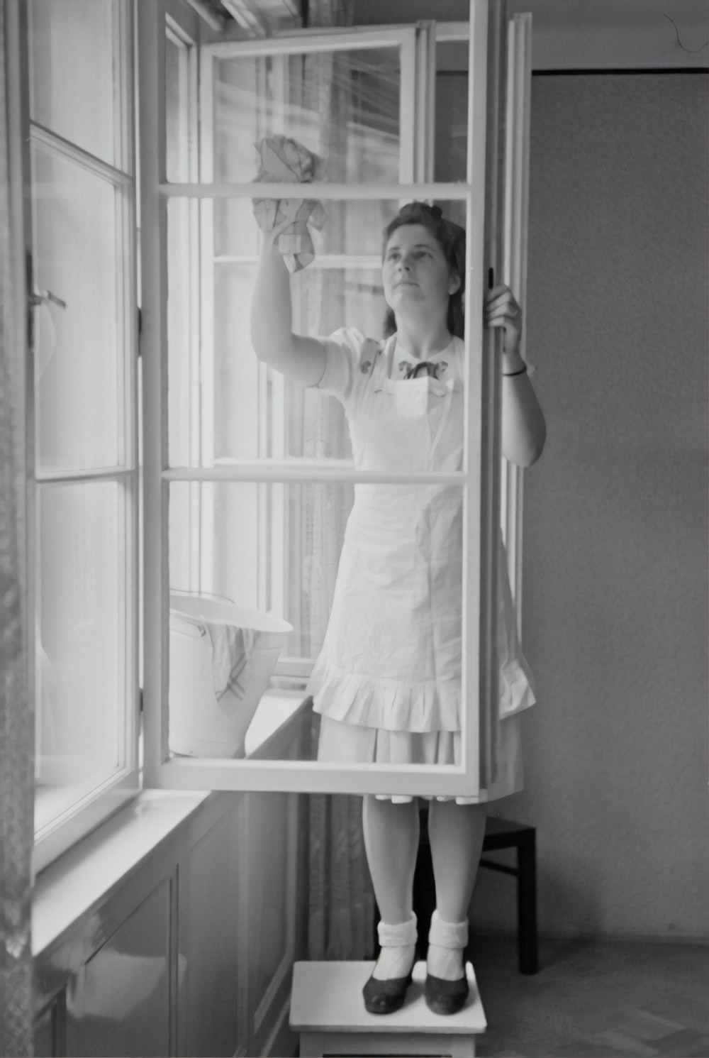 grayscale photography of woman cleaning glass window