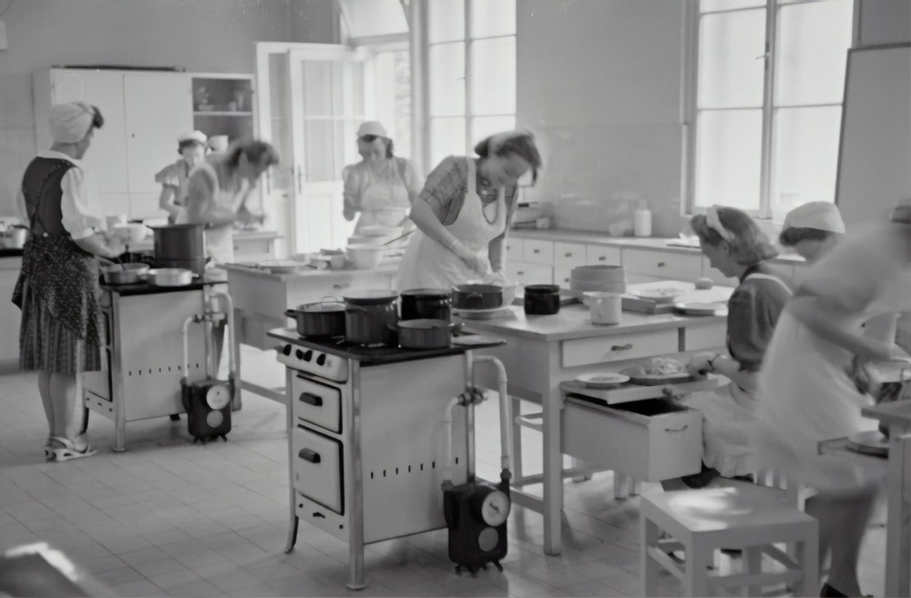 grayscale photography of women cooking in the kitchen
