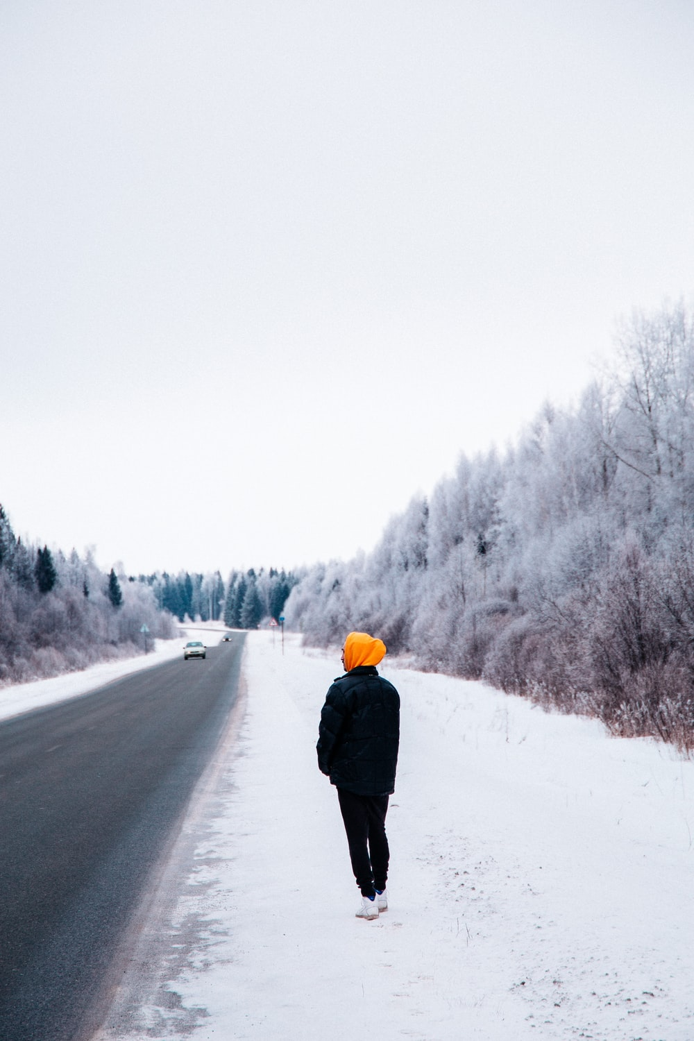 white vehicle on road and person walking on snowy field during daytime