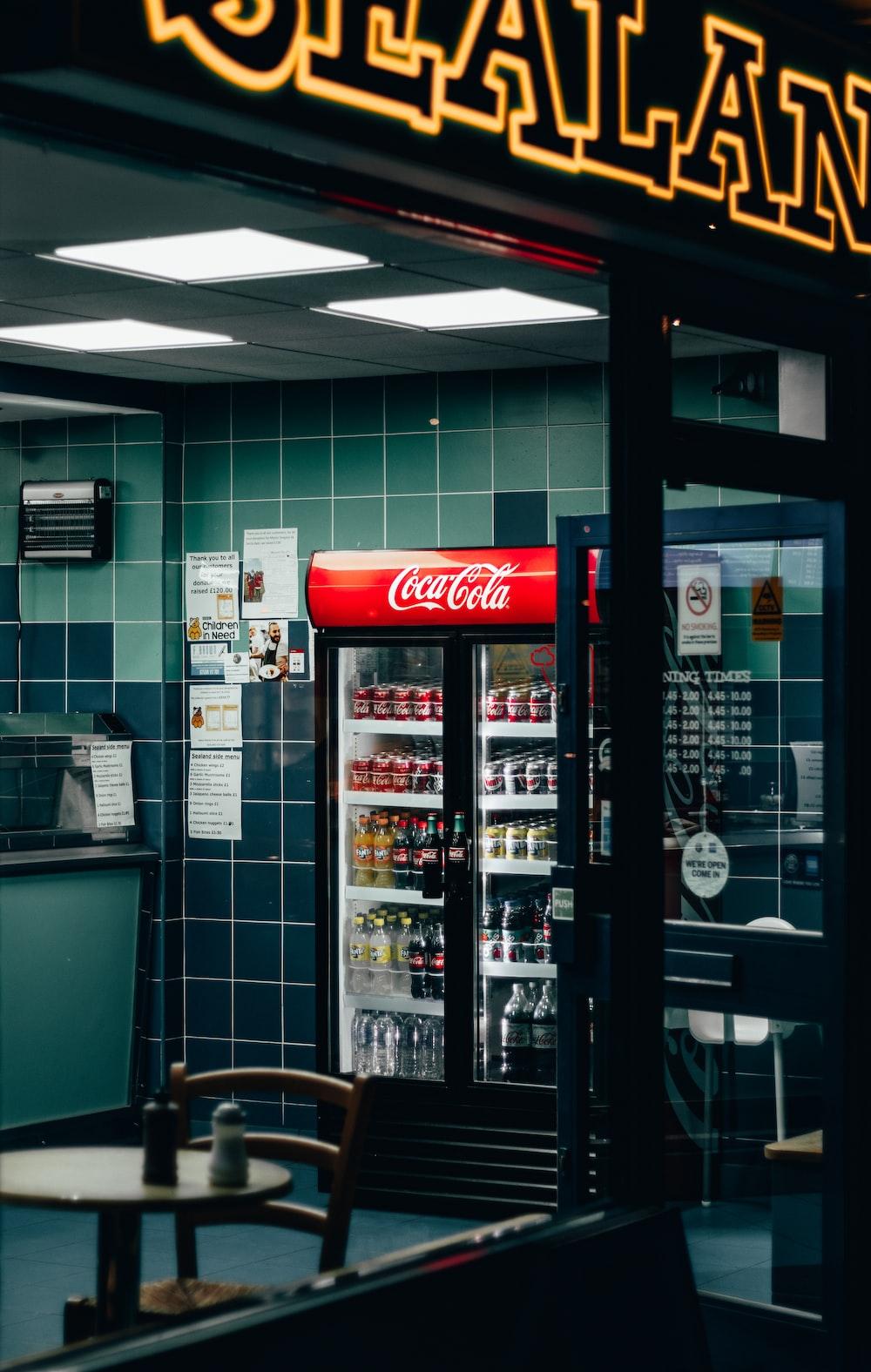 beverages in Coca-Cola beverage cooler inside shop during night