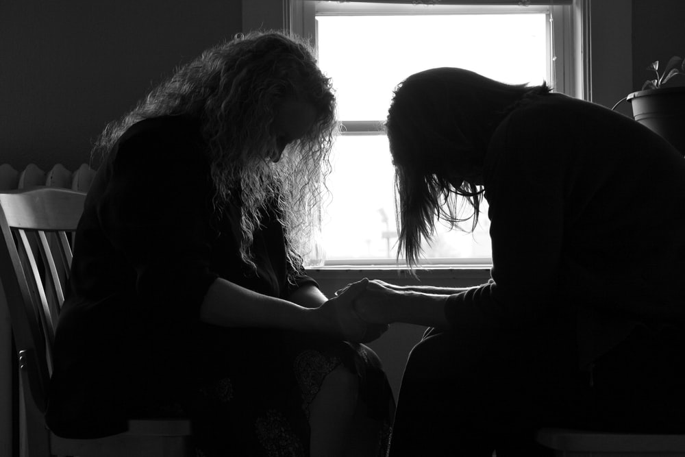 two sitting women holding hands each other while praying inside room