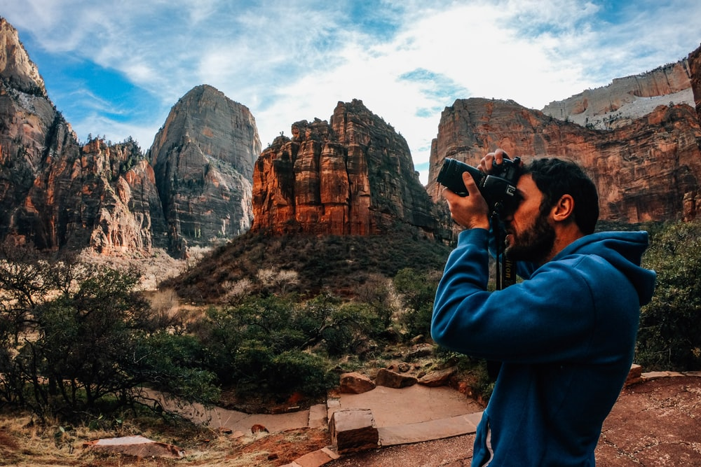 man using DSLR camera near shrubs and mountains during day