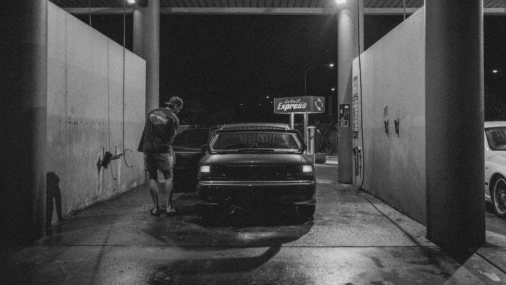 grayscale photography of car in car wash