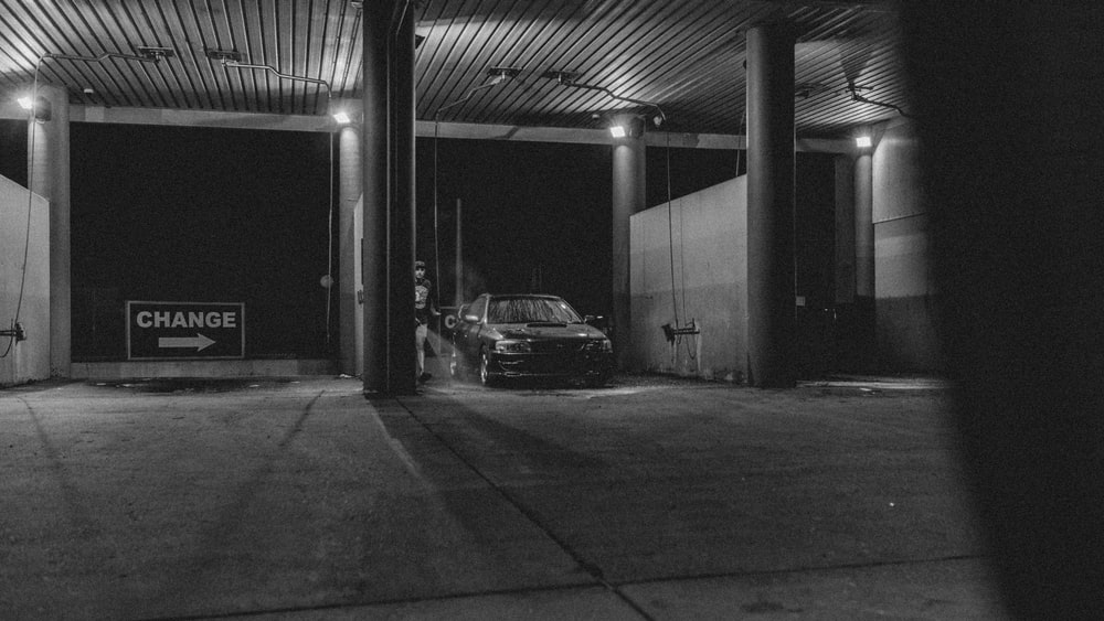grayscale photography of vehicle in car wash